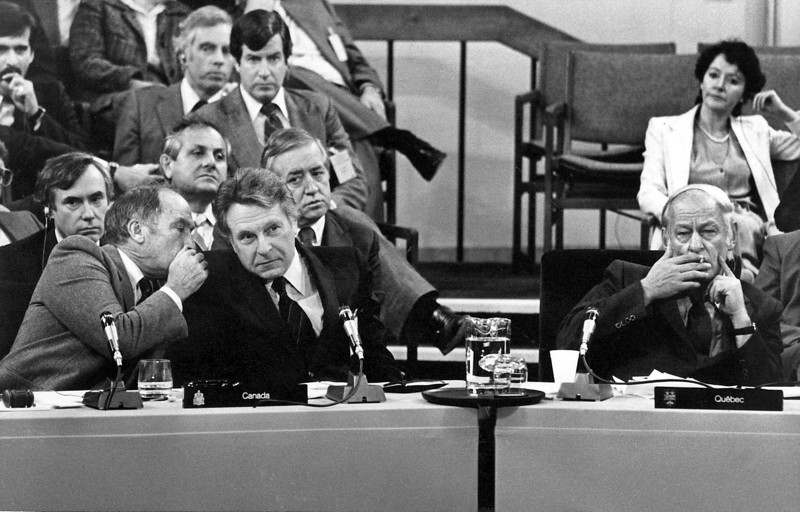 (OTT19) OTTAWA, Nov 5--Odd man out--Quebec Premier Rene Levesque quietly smokes as Prime Minister Trudeau confers with finance Minister Allan MacEachan during the closing session of the constitutional conference in Ottawa. (CP PHOTO/Fred Chartrand) 1981
