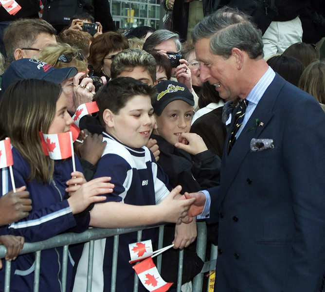Prince Charles greets school children gathered on the Sparks Street Mall, during a walkabout in Ottawa, Wednesday, April 25, 2001. The prince will visit Canada until Apr.30. (CP PHOTO/Fred Chartrand)