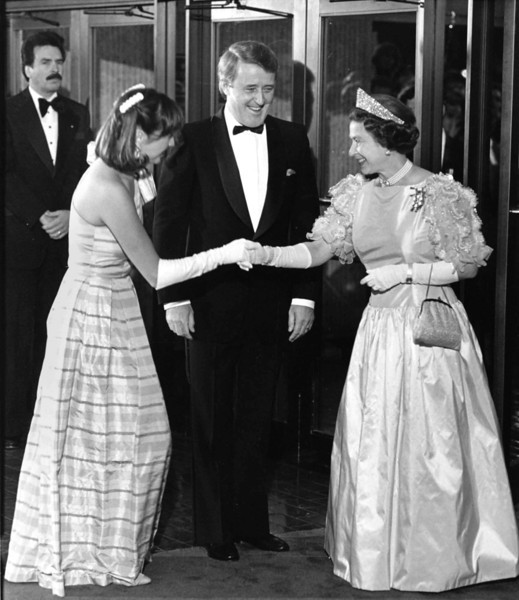 Prime Minister Brian Mulroney smiles while his wife Mila curtsies for Queen Elizabeth II as she arrived for a state dinner in Winnipeg on October 6, 1984. (CP Photo/Fred Chartrand)