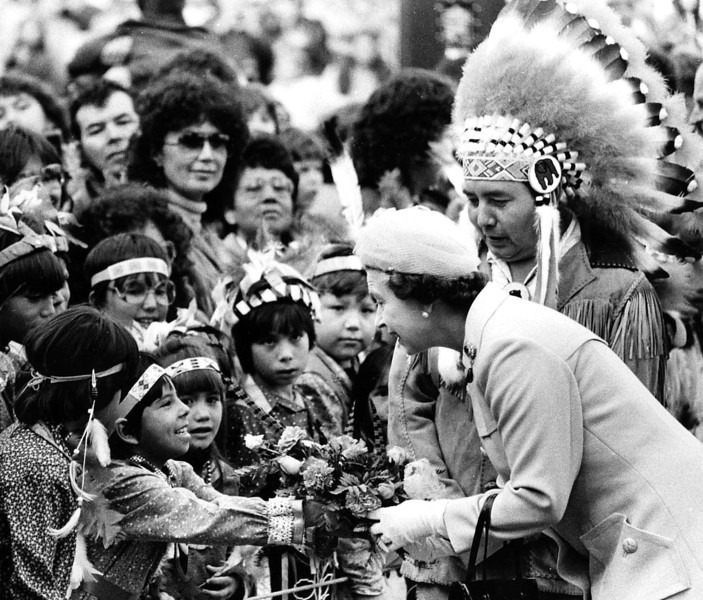 Accompanied by Chief Wellington Staats of the Six Nations Council of the Mohawks, Queen Elizabeth II accepts a bouquet from Indian children in Brantford, Ont., October 1, 1984. (CP Photo/Fred Chartrand)