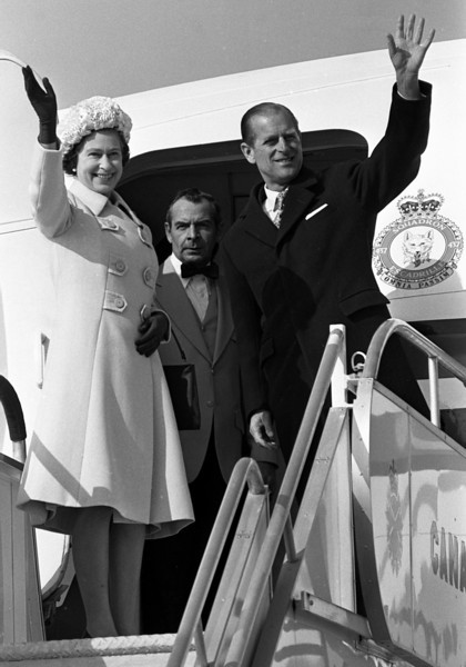 Queen Elizabeth II and Prince Philip wave good-bye to Ottawa from the door of the Canadian Forces jet that whisked them off to the Bahamas, Oct. 19, 1977, at the conclusion of their six-day visit to the capital. (CP PHOTO/Fred Chartrand)