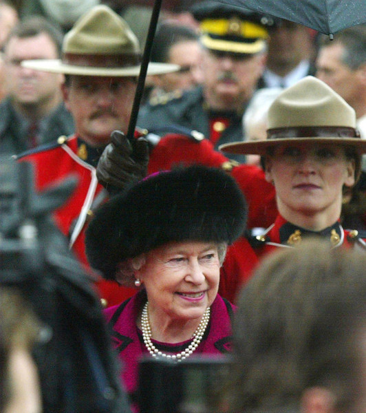 Queen Elizabeth II is followed by RCMP constables as she makes her way to an interfaith service on Parliament Hill, in Ottawa on Sunday Oct. 13, 2002. (CP PHOTO/Fred Chartrand)