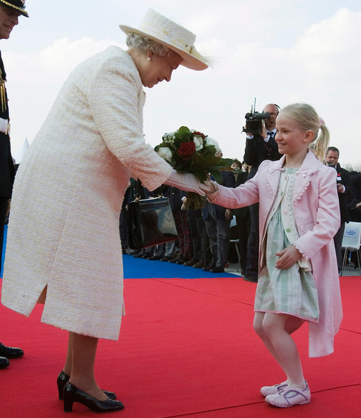 Rachel Harper, 6, daughter of Canadian Prime Minister Stephen Harper, curtseys as she presents flowers to Queen Elizabeth II during a ceremony marking the 90th anniversary of Canada's landmark First World War victory at Vimy Ridge, France, at the Vimy Ridge Memorial on Monday, April 9, 2007.(CP PHOTO/Fred Chartrand) Canada