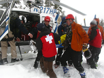 A combination of CHP, Ski Patrol and Search and Rescue volunteers load the survivor aboard a helicopter.