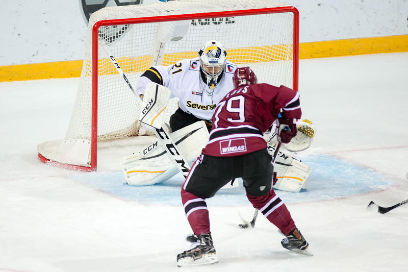 Vitalijs Pavlovs (79) tries to score against Jakub Kovar (21) of Severstal Cherepovets in the KHL regular championship game between Dinamo Riga and Severstal Cherepovets, played on January 3, 2017 in Arena Riga