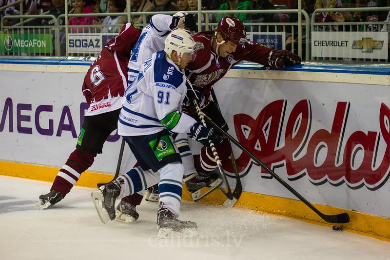 Sandis Ozoliņš un Arvīds Reķis pie apmales cīnās par ripu ar Dynamo Moscow hokejistiem
