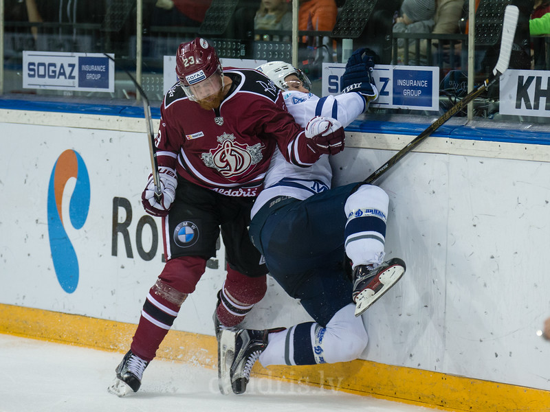 Aleksandrs Jerofejevs (23) of Dinamo Riga check Alexander Osipov (47) into the boards in the KHL regular championship game between Dinamo Riga and Dynamo Moscow, played on October 3, 2016 in Arena Riga