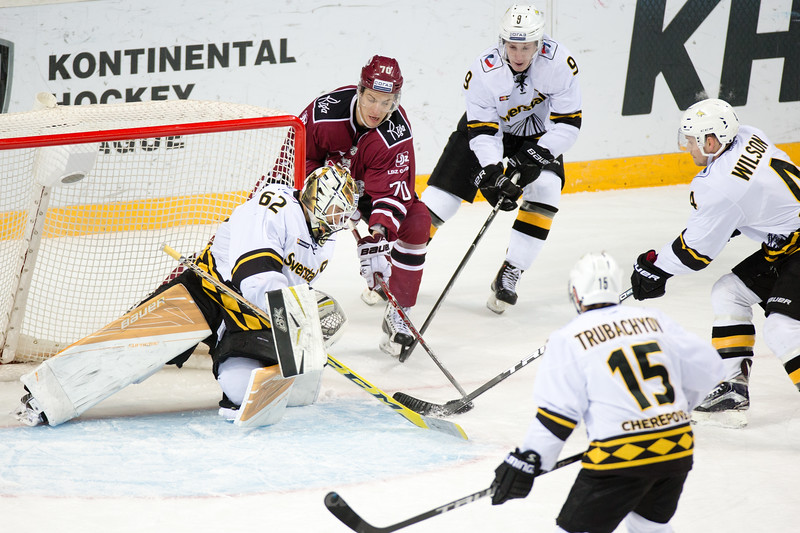 Miks Indrasis (70) tries to score to goalie of Severstal Cherepovets Roman Smiryagin (62) in the KHL regular championship game between Dinamo Riga and Severstal Cherepovets, played on January 3, 2017 in Arena Riga