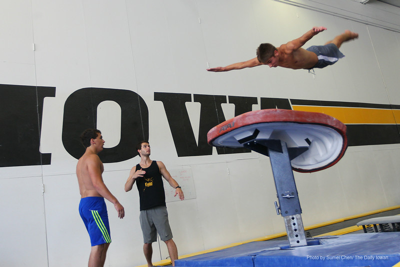 Iowa City, IA-  Elijah Parsells, 16, practices gymnastics techniques under Ben Ketelsen's (middle) guidance during Iowa Boy's Gymnastics Camp in Field House on Monday, July 9, 2012.(The Daily Iowan/Sumei Chen)