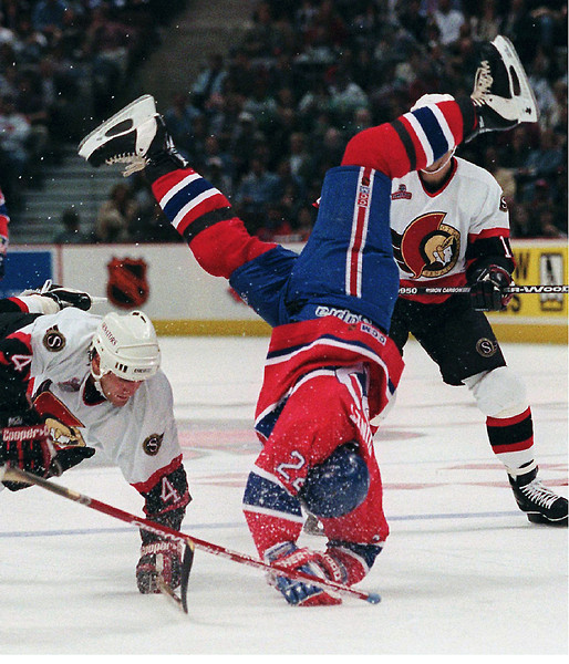 (OTTX 101) KANATA, ONT, MARCH 30--UP AND OVER--Montreal Canadian winger Benoit  Brunet goes up and over Ottawa Senators Sean Hill during first period NHL actionat the Corel Centre in Kanata, Ontario Saturday. (CP PHOTO) 1996 (stf/Fred      Chartrand)fxc