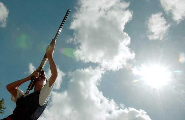 BJ Blanchard, 13, of Vidor, follows a bird out of the high house while shooting from station eight Friday afternoon during a practice round of skeet at the Orange Gun Club in Orange County. Blanchard, who routinely shoots 250 shells per day, has hopes of making a trip to Beijing for the 2008 Olympics.<br /> PHOTO/SCOTT ESLINGER                 JUNE 11, 2004
