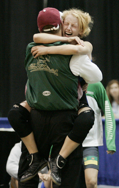 Krista Betts of Bass River, New Brunswick, jumps into her coach Patrick Zwicker's arms and becomes the first women to win a gold medal in the wrestling competition and the first medal winner for New Brunswick at the Canada Summer Games in Regina Thursday, August 18, 2005.(CP PHOTO/Fred Chartrand)