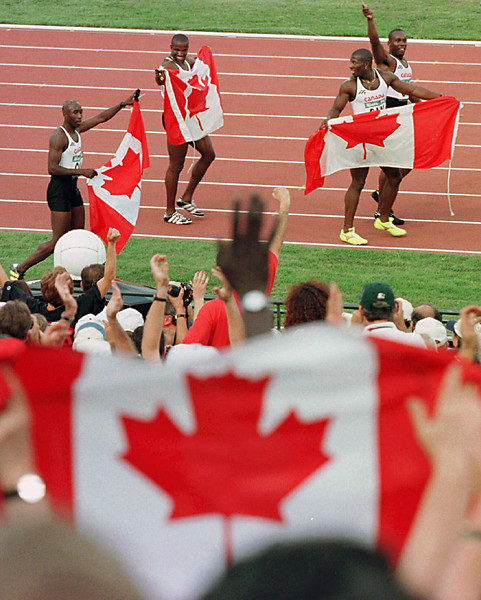 (CPAX 158) ATLANTA, August 3--A fan waves a Canadian flag as Robert Esmie, Donovan Bailey, Glenroy Gilbert and Bruny Surin, left to right, run their victory lap after winning the Olympic gold medal for the men's 4x100 metre relay at the Summer Olympic Games Saturday in Atlanta. (CP PHOTO) 1996 (stf/Fred Chartrand)