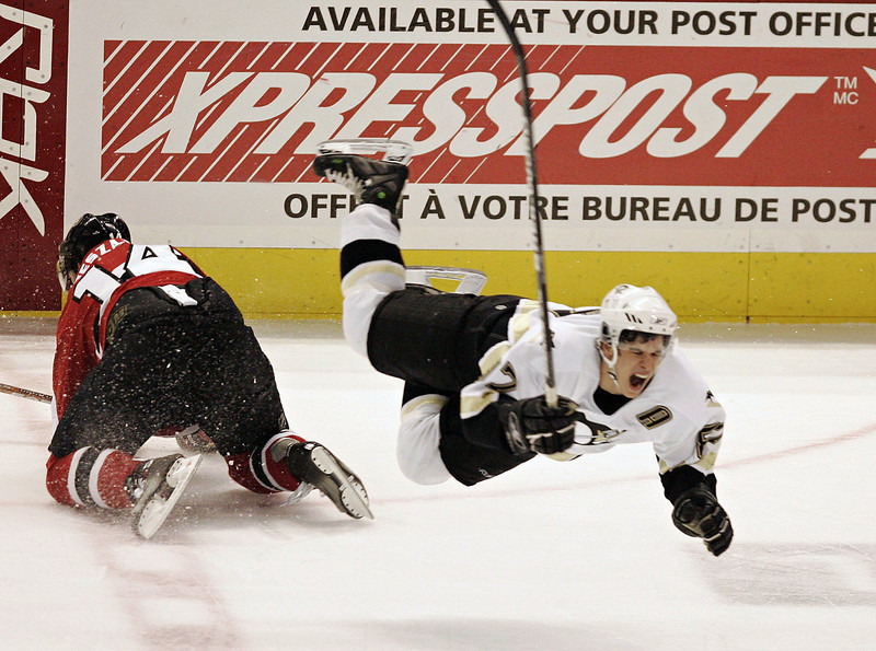 Pittsburgh Penguin Sidney Crosby winches as he flies through the air after being hit by Ottawa Senators Andrej Meszaros (14) from Povazka Bystrica, Slovakia during third period NHL hockey action in Ottawa, Tuesday March 21, 2006.(CP PHOTO/Fred Chartrand)