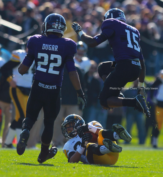 Iowa receiver Jordan Cotton catches a pass as two Northwestern defenders jump over him during the game at Ryan Field, in Evanston, Illinois on Saturday, October 27, 2012. Northwestern Wildcats defeated Iowa Hawkeyes, 28-17. (The Daily Iowan/Sumei Chen)