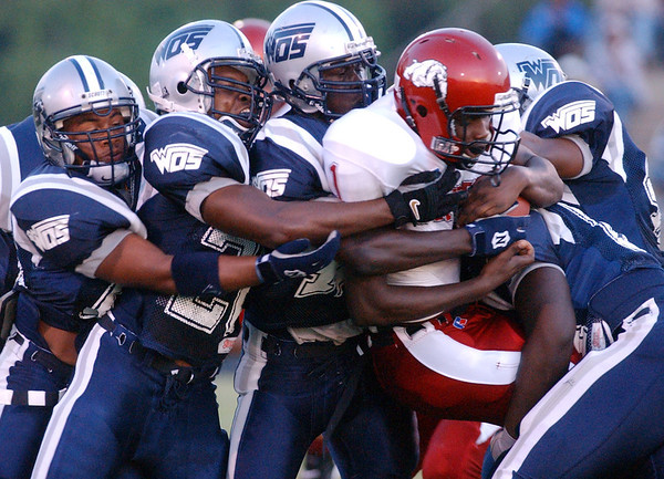 The West Orange-Stark High School defense wraps up Jasper quarterback Gilbert Moye (1) early in the first quarter Friday night at Mustang Stadium in Orange.<br /> PHOTO/SCOTT ESLINGER             AUGUST 27, 2004