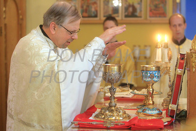 Fr. Daniel Gurovich raises his hands over the bread and wine during the consecration at St. Josaphat Ukrainian Catholic Church in Bethlehem, PA. photo/Don Blake Photography