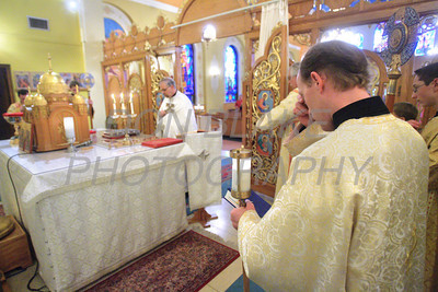 Seminarian Walter Pasicznyk makes the sign of the cross as Fr. Daniel Gurovich celebrates mass on the alter behind the icon screen during mass at St. Josaphat Ukrainian Catholic Church in Bethlehem, PA. photo/Don Blake Photography
