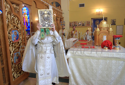 Fr. Daniel Gurovich carries the holy book on the alter behind the icon screen during mass at St. Josaphat Ukrainian Catholic Church in Bethlehem, PA. photo/Don Blake Photography