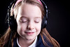 A cute little girl on a dark backtground listening to music on headphones