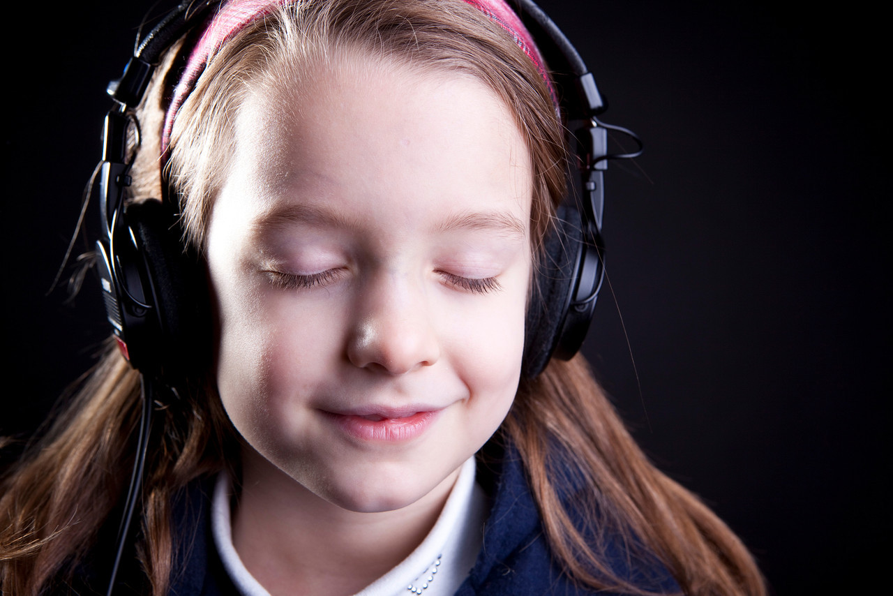 A cute little girl on a dark backtground listening to music on headphones