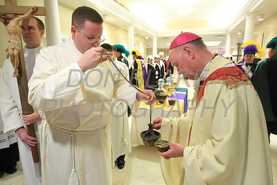 Bishop Malooly puts incense in the incensor as Seminarian Chris Coffiey holds it before  processing to the alter during Chrism Mass at Holy Cross Church in Dover, Del., Monday, April 2, 2012. photo/www.DonBlakePhotography.com