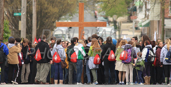 The cross is handed off to a new group on Maple Street in Wilmington, Del., during the 2012 Cross Pilgrimage March 31, 2012. photo/ www.DonBlakePhotography.com