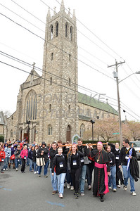 Bishop Malooly helps carry the cross as they leave St. Thomas the Apostle Church in the background during the 2012 Cross Pilgrimage March 31, 2012. photo/ www.DonBlakePhotography.com