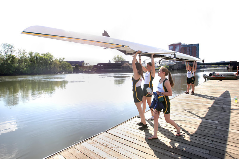 Members of St. Mark's Girls Crew Team prepare to lower the shell into the water during practice on the Christiana River, Thursday, April 19, 2012. photo/ www.DonBlakepPhotography.com