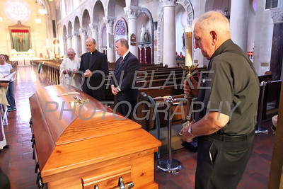 Br. MIchael Rosenello (right) holds a candle as Fr. Roberto Balducelli is blessed as the casket enters St. Anthony of Padua Church before the viewing, Tuesday, August 13, 2013. www.DonBlakePhotography.com