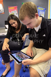 Social Studies teacher Jessica Shoja shows Luke Buzin 11th grade how to use the iPad at St. Elizabeth High School. photo/www.DonBlakePhotography.com