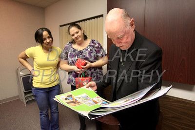 Bishop Malooly looks through a photo album that was a Christmas gift from the residents of Bayard House during Bishop Malooly annual Advent Dinner with the residents of Bayard House in Wilmington, Del. Bayard House a residential program serving homeless or transitional pregnant minors in Delaware. photo/Don Blake Photography.com