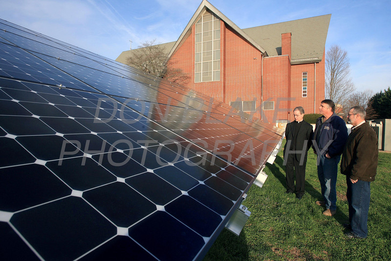 Fr. Charles Dillingham, Bruce Wanex, the parishioner who donated the panels, and Dave DeGhetto (facility manager) check out the new solar panels next to St. Mary of the Assumption Church. photo/Don Blake Photography.com