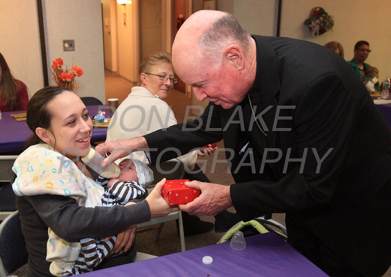Bishop Malooly holds one week old Alijah Sutton's bottle for is mother Kala Sutton as he gives her a Christmas gift during Bishop Malooly annual Advent Dinner with the residents of Bayard House in Wilmington, Del. Bayard House a residential program serving homeless or transitional pregnant minors in Delaware. photo/Don Blake Photography.com