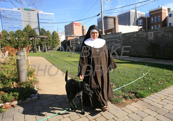 Sr. Maria Elena Romero walks with Salome one of the Sisters two dogs in the court yard at the Capuchin Poor Clares, St. Veronica Giuliani Monastery in Wilmington. photo/Don Blake Photography.com