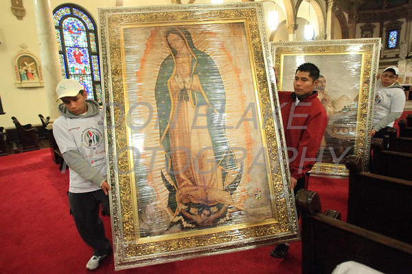 Runners participating InternationalÊGuadalupeÊTorch Run  prepare to load the large image of Our Lady of Guadalupe in the back of a truck before they start their run at St. Paul Church, Wednesday, December 7, 2011. The pilgrimage is carried out in a relay style from Mexico City, Mexico to New York City. Runners will carry the torch more than 3,800 miles from Mexico and are scheduled to arrive in New York Dec. 12, the feast of Our Lady of Guadalupe. photo/Don Blake Photography.com