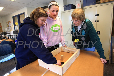 Volunteer Julie Dugan helps 7th graders Gabriella Santacecilia (left) and Jenn Sirillo with a science olympiad project at St. Ann School . photo/Don Blake Photography.com