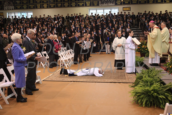 Mike Vogt prostrates him self as Bishop Malooly, his parents (left) and all in attendance pray during his Ordination in the Gym of Salesianum School, Wilmington, Del., Friday, January 27, 2012. Mike Vogt ask Bishop Malooly for permission to have his Ordination in the gym of Salesianum School where he is a teacher. photo/Don Blake Photography.com