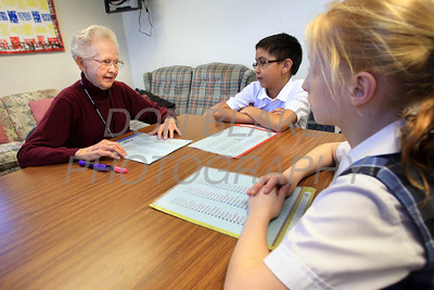 Volunteer Lyn Simpson helps 3rd graders Brandon Bacal and Olivia Sheetz with spelling at St. Ann School . photo/Don Blake Photography.com