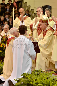 Mike Vogt kneels before Bishop Malooly as he receives the paten and chalice during his Ordination in the Gym of Salesianum School, Wilmington, Del., Friday, January 27, 2012. Mike Vogt ask Bishop Malooly for permission to have his Ordination in the gym of Salesianum School where he is a teacher. photo/Don Blake Photography.com