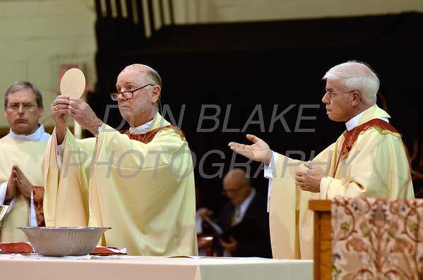 Bishop Malooly (left) along with Fr. Mike Vogt bless the host during his Ordination in the Gym of Salesianum School, Wilmington, Del., Friday, January 27, 2012. Mike Vogt ask Bishop Malooly for permission to have his Ordination in the gym of Salesianum School where he is a teacher. photo/Don Blake Photography.com