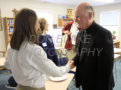 Bishop Malooly shakes hands with a student during his visit to Ss. Peter and Paul High School, January 11, 2012. photo/Don Blake Photography.com