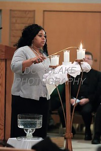 Ebonique Conkey a parishioner of New Mt. Calvary Baptist Church lights a candle during a Community Prayer Service for Justice, Non-Violence, and Respest for Human Dignity at St. Catherine of Siena, Tuesday, January 17, 2017. wwwDonBlakePhotography.com