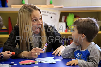 Teacher Holly Zorn help Alex Pate with his glue at Holy Cross School. www.DonBlakePhotography.com