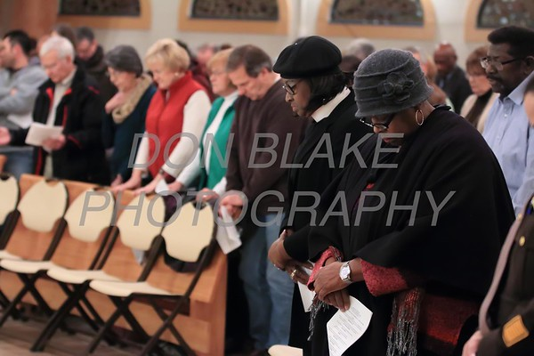 People pray during a Community Prayer Service for Justice, Non-Violence, and Respest for Human Dignity at St. Catherine of Siena, Tuesday, January 17, 2017.