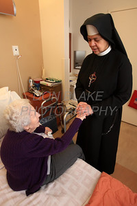 Sr. Mary Daniel prays with McGowan who was a long time parishioner of Sacred Heart Church and is now a resident at Kentmere Nursing and Rehabilitation Center. photo/Don Blake Photography.com