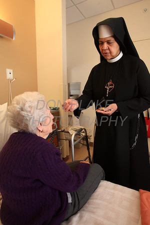 Sr. Mary Daniel gives communion to McGowan who was a long time parishioner of Sacred Heart Church and is now a resident at Kentmere Nursing and Rehabilitation Center. photo/Don Blake Photography.com