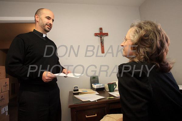 Fr. John Grimm, Pastor at Holy Spirit Parish talks with parish secretary Marie Redfield. photo/Don Blake Photography