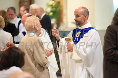Fr. John Grimm, Pastor at Holy Spirit Parish distributes communion during mass. photo/Don Blake Photography