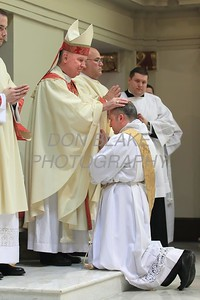 Lance Martin kneels as Bishop Malooly lay hands on his head during his Ordination at the Cathedral of St. Peter, Saturday, May 28, 2016. wwwDonBlakePhotography.com